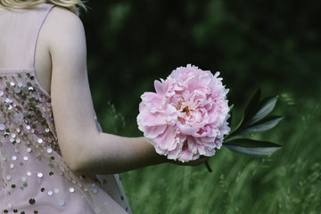 A child in a sequinned dress holding a large pink peony.