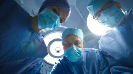 Low Angle Shot of Team of Doctors and Nurses looking Into camera. Patient Point of View.