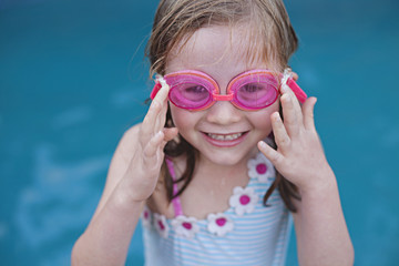 A young girl puts on her pink goggles ready to to go swimming