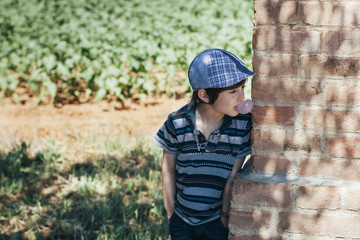 Boy peeking from behind a wall with chewing gum bubble in his mouth