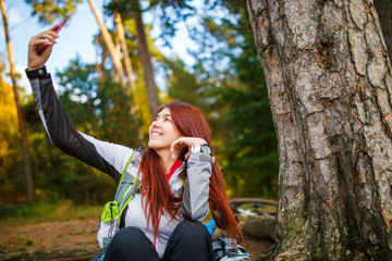 Photo of happy woman photographing herself in autumnal forest