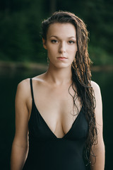 A portrait of a beautiful brunette with long wet hair after a swim