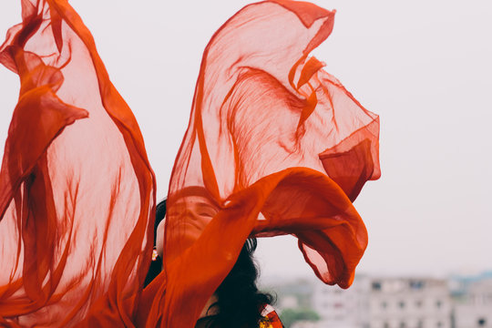 young happy woman flying orange color scarf