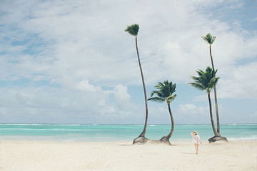 Woman walking on tropical beach with palm trees