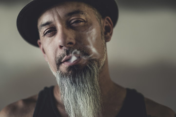 Rugged man with tattoos smokes and gesticulates