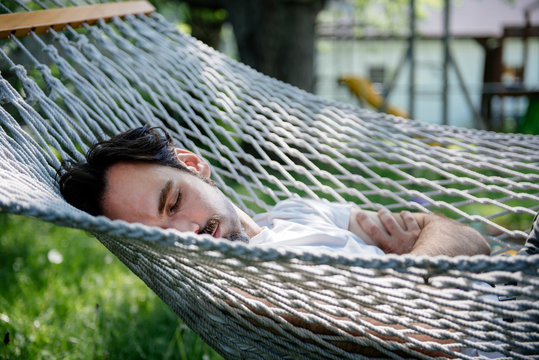 Man takes a nap in a hammock on a sunny summer day