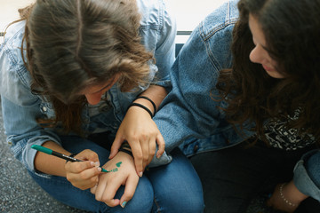 Girl painting a girlfriend's hand