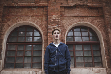 Young man with earphones standing at brick building
