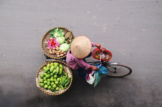 Aerial view of a Vietnamese traditional seller on the bicycle with bags full of vegetables