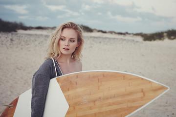 Surfer Girl holding board on empty beach