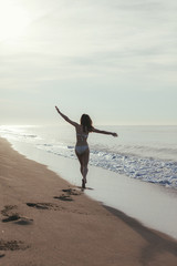 Beautiful woman running and having fun with extended arms on the beach. Freedom.