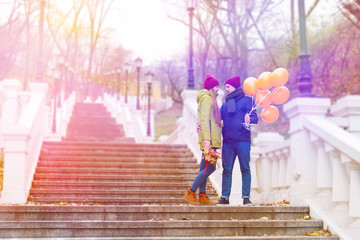 Boyfriend with orange balloons have dating with girlfriend in park in autumn. Couple in love