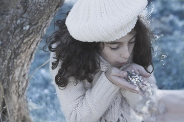 Girl blowing  glitters from her hand in Winter