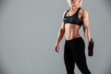 Cropped photo of strong blonde sports woman holding bottle of water,