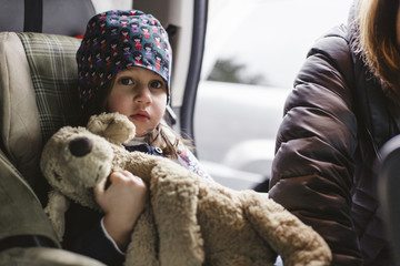 A young girl is strapped into a car seat by her mother.