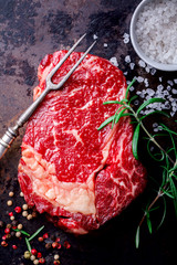 Raw Fresh Marbled Meat Beef Steak. Herbs and Seasonings on Dark  Background  Rosemary Pepper and Salt Ingredients for Cooking  Top View