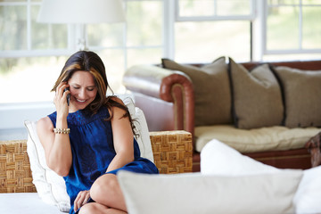 Hispanic woman talking on cell phone in living room