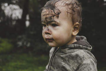 Cute young toddler boy outside in the rain with face covered in mud - funny