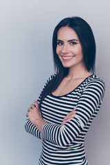 Portrait of caucasian entrepreneur in casual black and white outfit on light grey background, with nice natural light make up, long dark straight hair, smooth nice skin, beaming smile