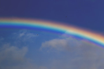 colorful rainbow with dramatic storm sky above and serene sky below