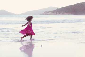 Young girl in pink playing on the beach