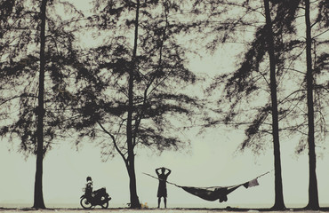 Silhouette of a young men with crossed hands above his head camping/hammocking in the nature