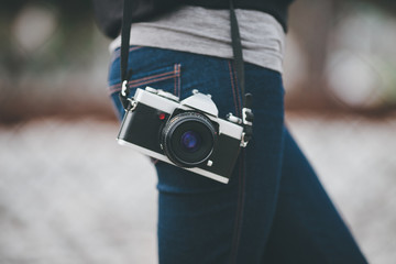 Mid section of woman holding film old camera