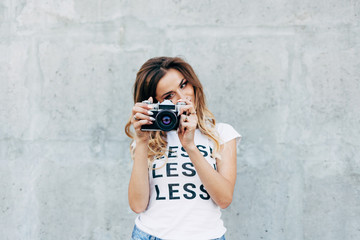 """Stylish woman photographer in white T-shirt with word """"less"""" with retro camera on the gray wall background"""