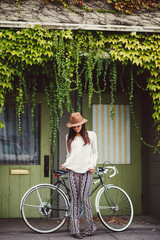 Beautiful young woman standing with her bike in a ivy doorway