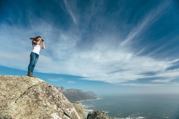 Female hiker enjoying the view from a mountain top with binoculars