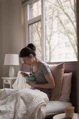 Relaxed woman having fruit while reading book on bed