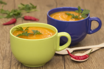 A bright cream soup of pumpkin on a wooden table.