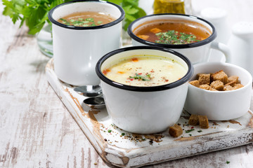 assortment of hot soups in mugs on wooden board
