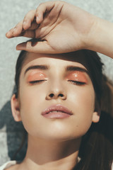 Sunlit face of a young woman with closed eyes