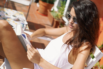 beautiful brunette woman reading a book at her home balcony in Barcelona