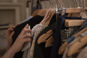 Cropped hand of woman with phone choosing clothes
