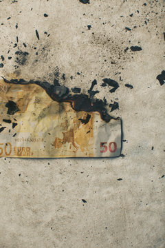 Burning fifty euro banknote.