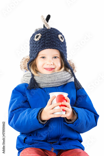 5de36dc090c3 Vertical portrait of cute child in winter clothes with tea paper cup ...