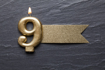 Gold number 9 celebration candle with glitter label