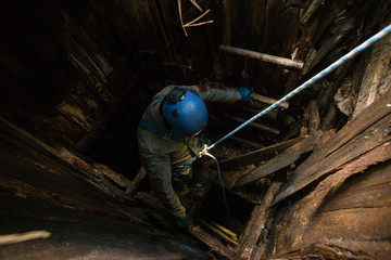 Miner on rope exploring the old mine shaft