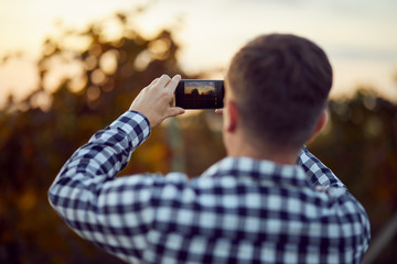 Back view of young man taking photo with digital camera on mobile phone of nature landscape