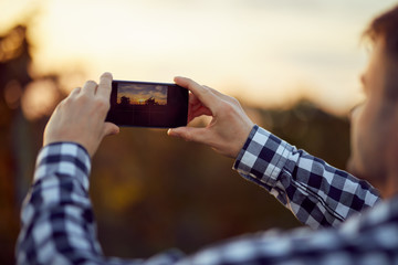 Back view of man taking photo with digital camera on mobile phone of sunset