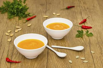 A  vegetarian cream soup of pumpkin on a wooden table.