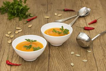A  vegetarian cream soup of pumpkin on a wooden table. Soft focus.