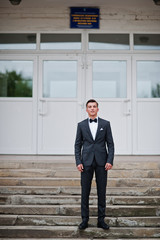 Portrait of a handsome high school graduate in stylish tuxedo posing on the stairs on the prom.
