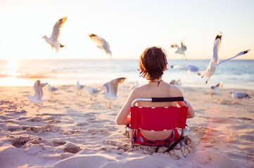 Child sitting at the beach surrounded by seagulls
