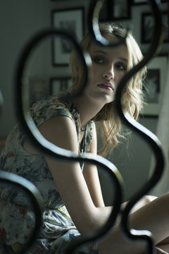 Young pensive 18 year old girl sitting in her bedroom and seen through her bed post