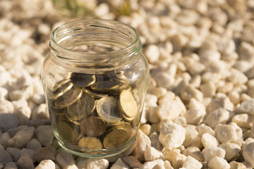 A transparent jar with many coins saved