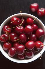white bowl of cherries on black table