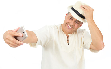 Smiling man makes self portrait. Selfie. Traveler is wearing comfortable white hippie robe..